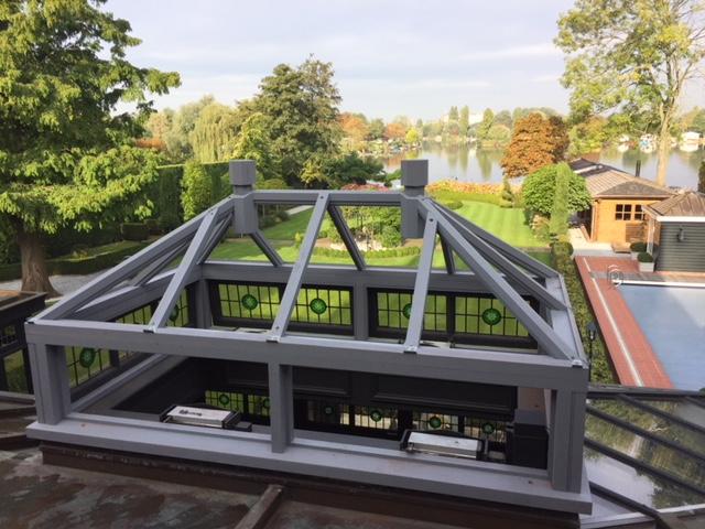 dak koepel met glas met een werkje erin, met op de achtergrond een tuin.